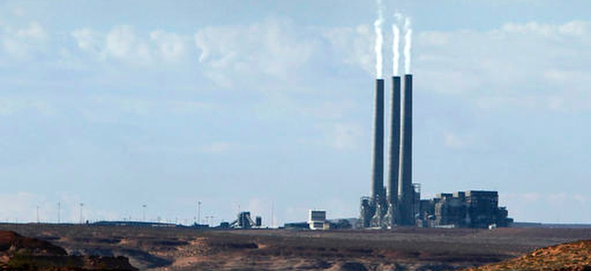 In this Sept. 4, 2011, file photo, smoke rises from the stacks of the main plant facility at the Navajo Generating Station, as seen from Lake Powell in Page, Ariz.
