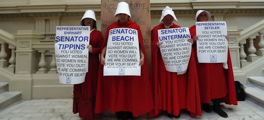 Women hold signs to protest HB 481 in April at the state Capitol in Atlanta. HB 481, which would ban most abortions after a fetal heart beat is detected, was signed by Gov. Brian Kemp in May.