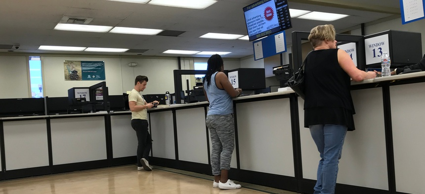 People standing at the counter inside the DMV field office in Culver City, California.
