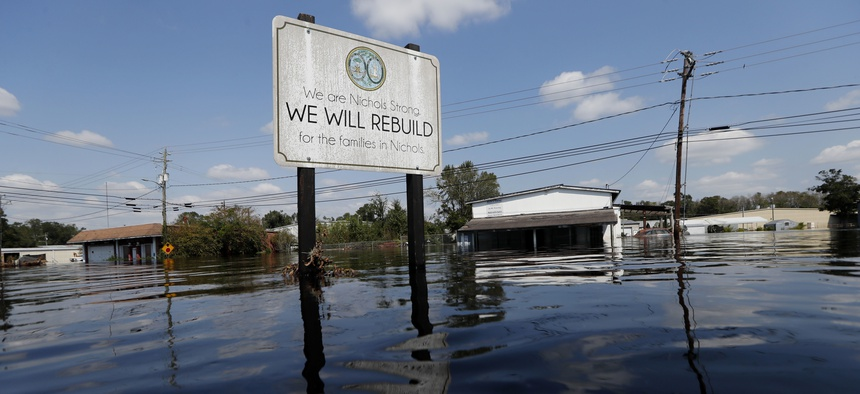 A sign commemorating the rebuilding of the town of Nichols, which was flooded two years earlier from Hurricane Matthew, stands in floodwaters in the aftermath of Hurricane Florence in Nichols, S.C. in 2018.