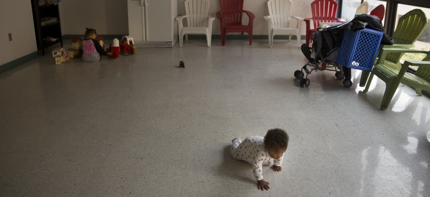 A baby crawls toward her mother at a homeless shelter in Los Angeles.