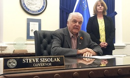 Nevada Gov. Steve Sisolak sits at his desk at the Capitol in Carson City in May. Sisolak says he plans to sign legislation expanding collective bargaining rights for public workers in the state.
