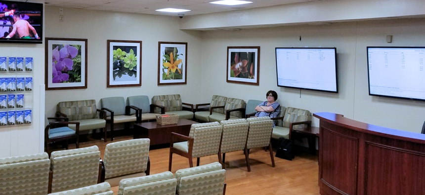 A lone woman sits in a hospital waiting room.