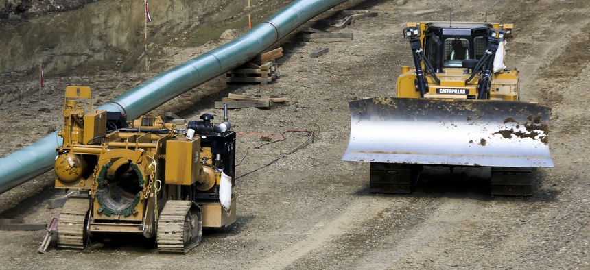 An operator moves a bulldozer along a section of assembled pipe lined up along a cleared section of woods where a pipeline for shale gas is under construction on Saturday, July 8, 2017, in Jackson Township, Pa.