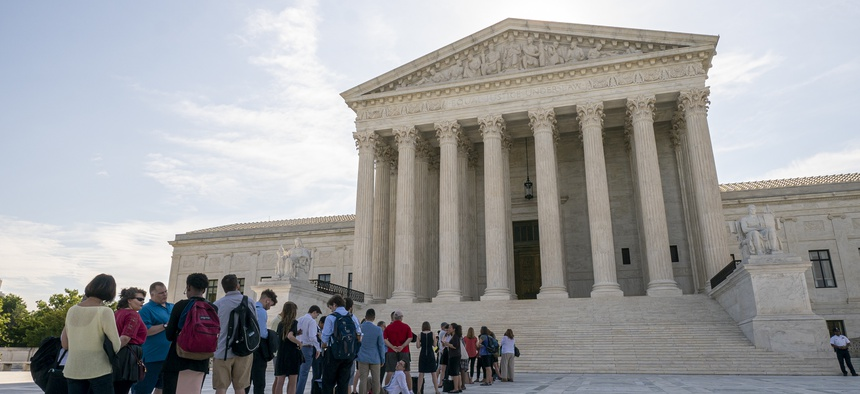 Visitors line up at the Supreme Court in Washington as the justices prepare to hand down decisions, Monday, June 17, 2019.