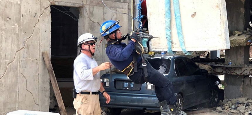 Instructor Richard Wier, left, advises New Jersey Transit Police Officer Juan Guallpa as he works to secure a dangling 1,200-pound concrete slab in Disaster City, a training site for first responders at Texas A&M University in College Station.