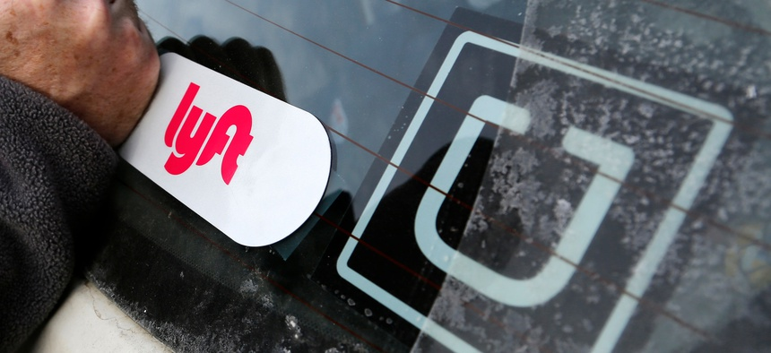 In this Jan. 31, 2018, file photo, a Lyft logo is installed on a Lyft driver's car next to an Uber sticker in Pittsburgh.
