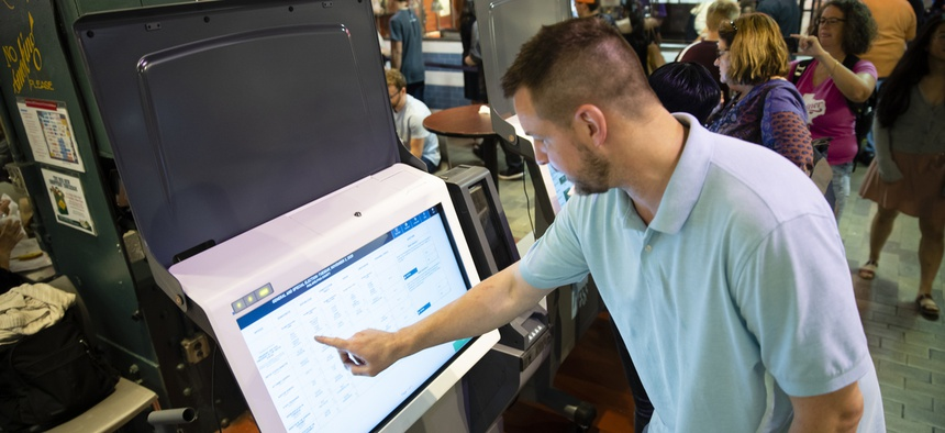 A Philadelphia investigator demonstrates new voting machines. Pennsylvania is one of several states replacing election equipment before the 2020 presidential election.