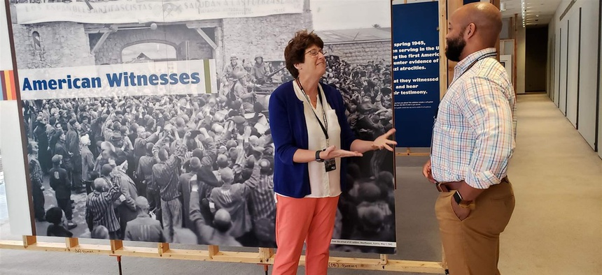 Kim Kenneson of Johnson City, Tennessee, and Nicholas Turner of Zachary, Louisiana, at the U.S. Holocaust Memorial Museum in Washington, D.C. The teachers discuss teaching the Holocaust in front of a mural about the American reaction to the Holocaust.