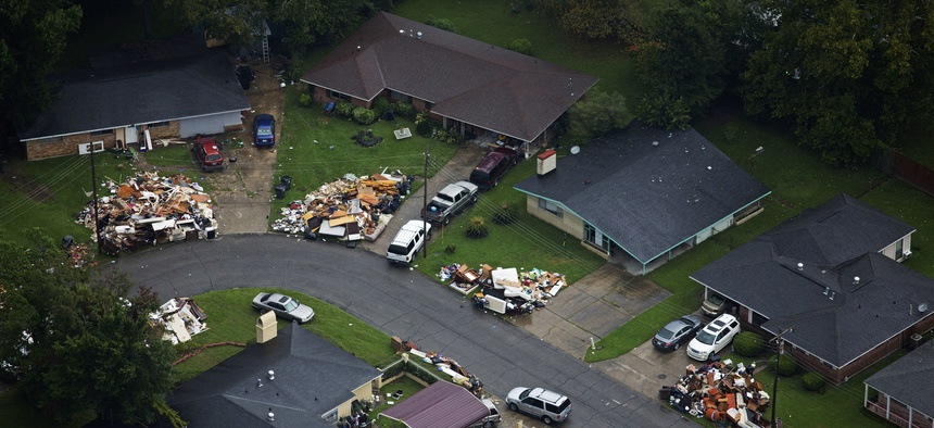 In this Aug. 25, 2016 photo, debris from gutted homes line the streets of Baton Rouge, La.