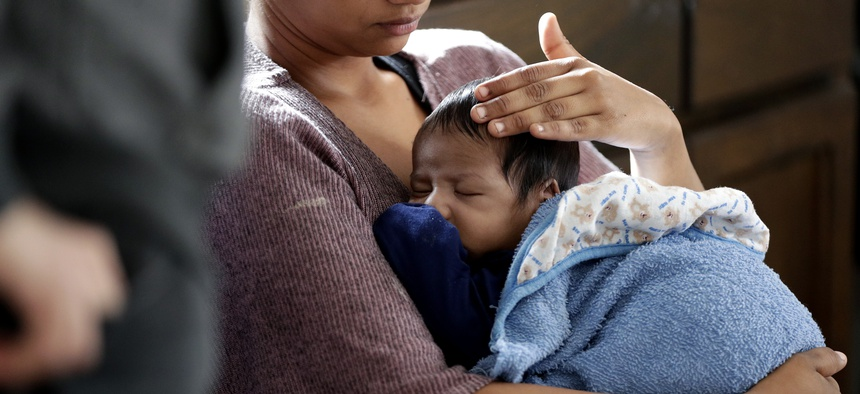A mother holds her one-month old son during a medical checkup after being released from a Border Patrol facility.