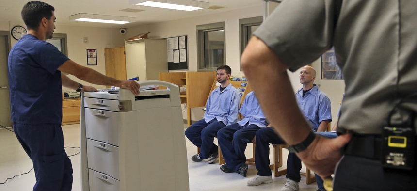 Several Franklin County Jail inmates are watched by a nurse and a corrections officer after they received their daily doses of buprenorphine, a drug which controls heroin and opioid cravings.