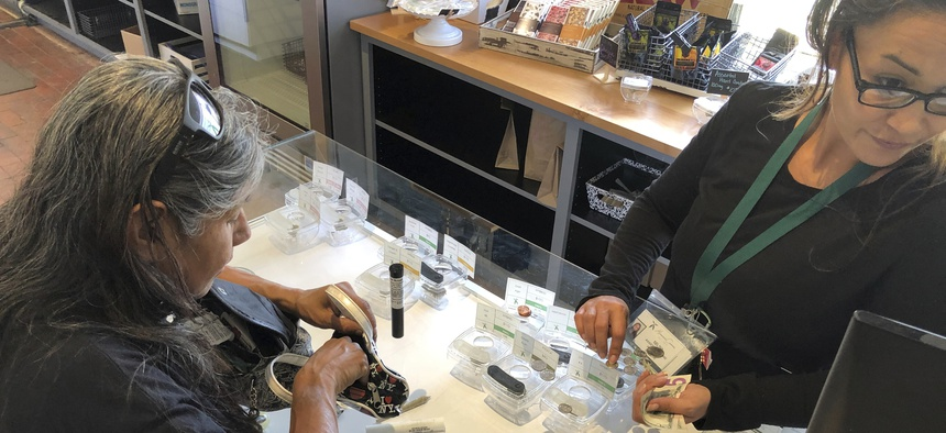 An assistant manager at Minerva cannabis dispensary sells a vial of marijuana to a customer who uses cannabis to relieve chronic pain, in Santa Fe, N.M.