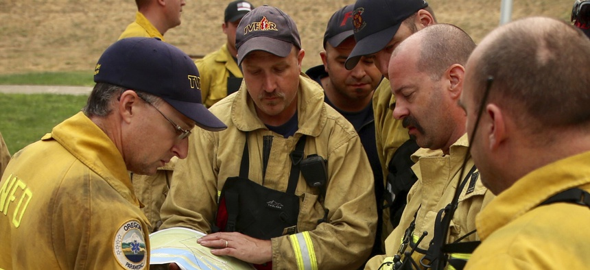 Firefighters combatting a wildfire consult a map of the area. A new technology aims to give fire departments 3-D maps of buildings.