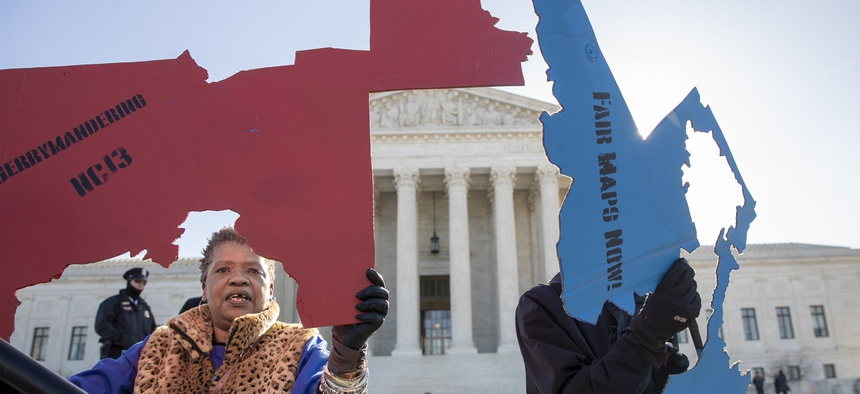 Activists at the Supreme Court opposed to partisan gerrymandering hold up representations of congressional districts from North Carolina, left, and Maryland, right, in March 2019.