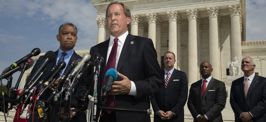 Texas Attorney General Ken Paxton, center, with District of Columbia Attorney General Karl Racine, left, and a bipartisan group of state attorneys general announces an antitrust investigation of big tech companies. an