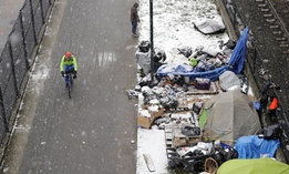 A bicyclist rides past a homeless encampment as snow falls, Friday, Feb. 8, 2019, in Seattle.