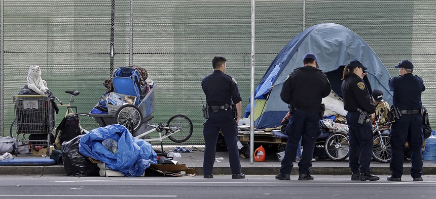 San Francisco police officers wait while homeless people collect their belongings.  In June, city officials adopted legislation to set up a program allowing people with mental illness and addiction to be forced into treatment.