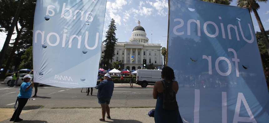 Supporters of California Assembly Bill 5 display banners in support of the bill during a rally at the Capitol in Sacramento, Calif., Wednesday, Aug. 28, 2019.