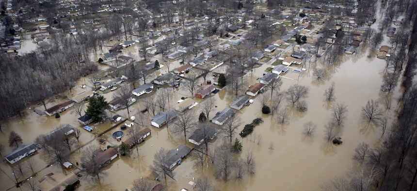 In this aerial photo, houses are surrounded by floodwater, Thursday, Dec. 31, 2015, in Arnold, Mo.