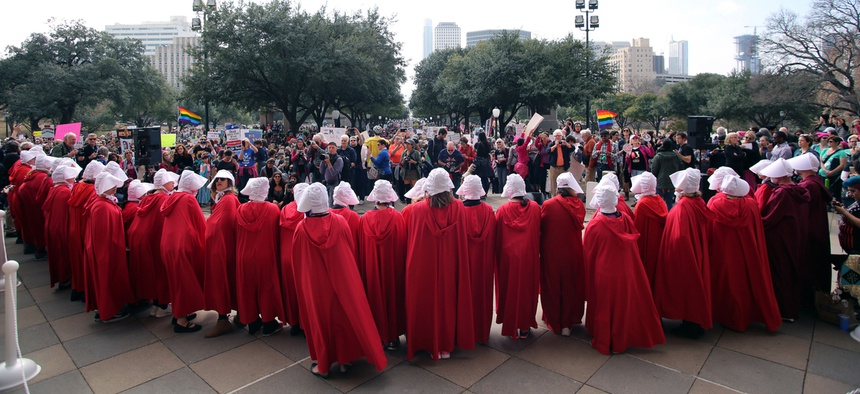 "Women dressed in ""Handmaids Tale"" costumes stand on the steps of the state Capitol at the start of a rally for reproductive rights."