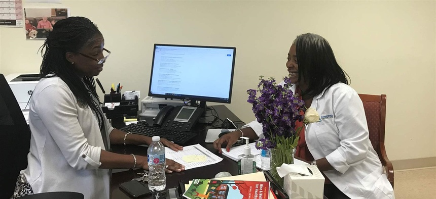 Lisa Mears-Morris, left, and Latonya Gwynn go over resident files at Weinberg Villages, a housing complex for low-income seniors in Owings Mills, Maryland. The two are part of a national experiment aimed at helping seniors age in place.