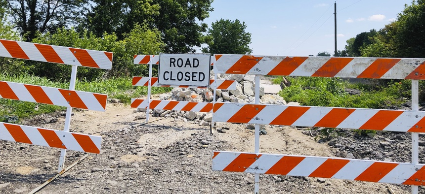In this July 27, 2019, photo, signs block access to a bridge on a rural road in Callaway County, Missouri, on July 27, 2019. The road's approach to the bridge was washed out by flooding that began in late May and extended into early July.