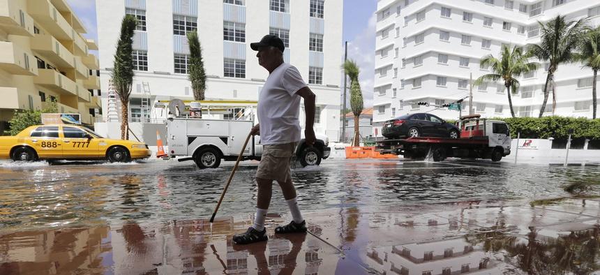 A man walks along a flooded street in Miami Beach, Fla.