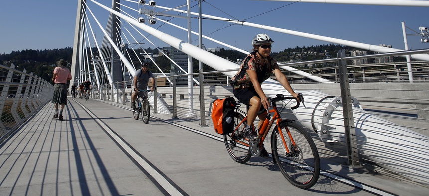 Runners and cyclists make their away across the Tilikum Crossing, a bridge in Portland, Ore.