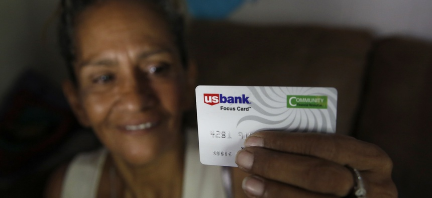 Susie Garza displays the city provided debit card she receives monthly through a trial program in Stockton.