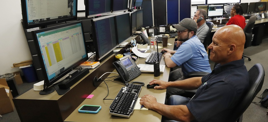 In this Sept. 12, 2019, photo, monitors check screens in the Governor's Office of Information Technology in Denver. Some cybersecurity professionals are concerned insurance policies designed to mitigate ransomware attacks might be encouraging hackers.