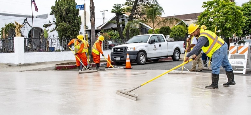 Workers apply CoolSeal to a street in Pacoima in June.