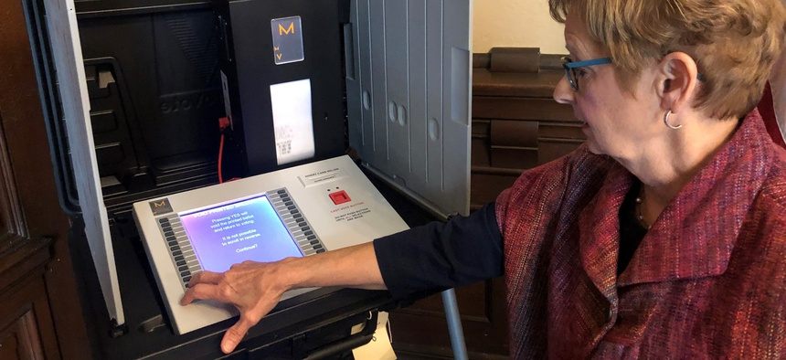In this Sept. 25, 2019 photo, Indiana Secretary of State Connie Lawson demonstrates an upgraded voting machine on Wednesday, Sept. 25, 2019, at the Indiana Statehouse office in Indianapolis.
