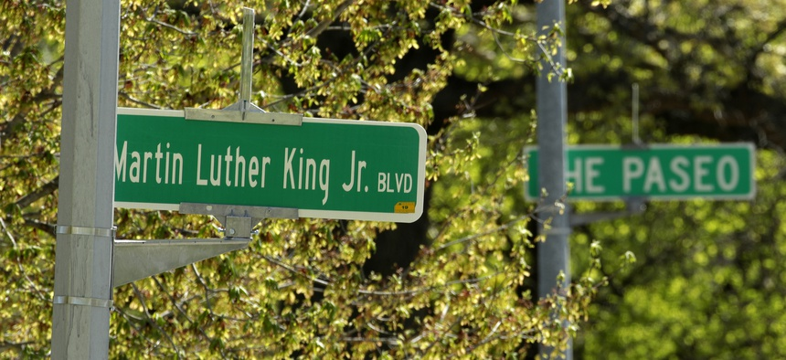 In this photo taken April, 20, 2019, a newly changed sign for Dr. Martin Luther King, Jr. Boulevard stands in contrast to a yet-to-be changed sign for The Paseo in Kansas City, Mo.