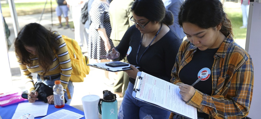 Arizona students fill out voter registration forms at Phoenix College on National Voter Registration Day Tuesday, Sept. 24, 2019.
