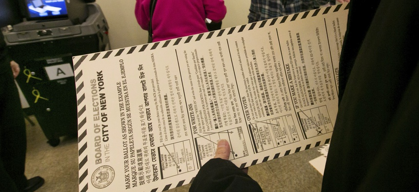 In this file photo, a voter carries her ballot to be scanned at a polling place in New York's Chinatown neighborhood. A ballot measure will give New York City residents a chance to institute ranked choice voting in primaries and special elections.