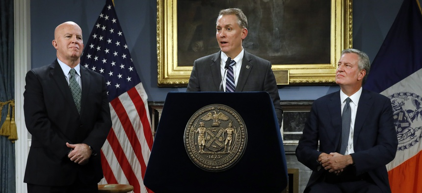 New York City Police Commissioner James O'Neill, left, listens as his successor, Chief of Detectives Dermot Shea, center, speaks at New York City Hall, while New York Mayor Bill de Blasio looks on.