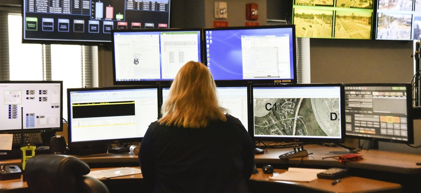 A dispatcher works at a desk station with a variety of screens used by those who take 911 emergency calls in Roswell, Ga.