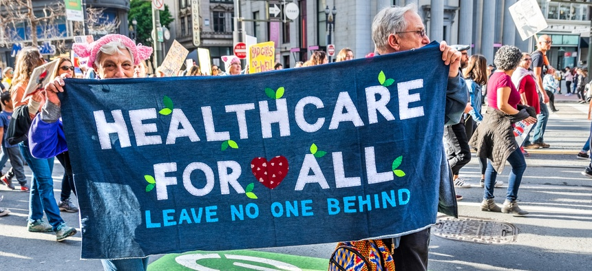 "Participants to the Women's March event carry ""Healthcare for all"" sign while marching on Market street in downtown San Francisco in January 2019."