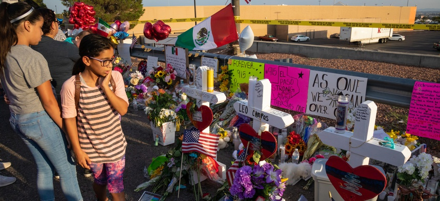 Mourners stand by memorials to the 22 people killed in a mass shooting in El Paso, Texas in August. The FBI data showed a 14% rise in anti-Latino hate crimes, the third year of increases of these types of offenses.