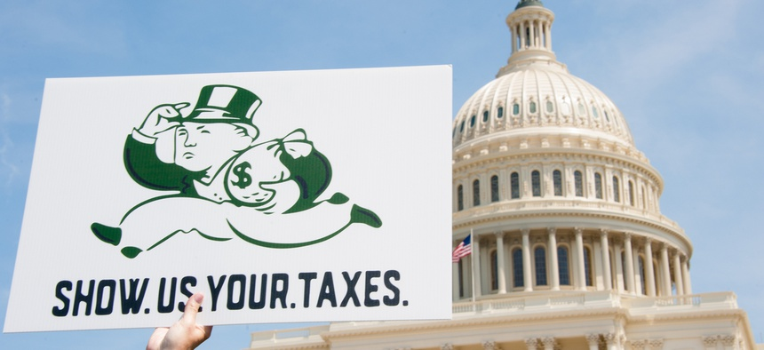 A protester holds a sign at the 2017 Tax March, where participants called on President Trump to release his tax returns.