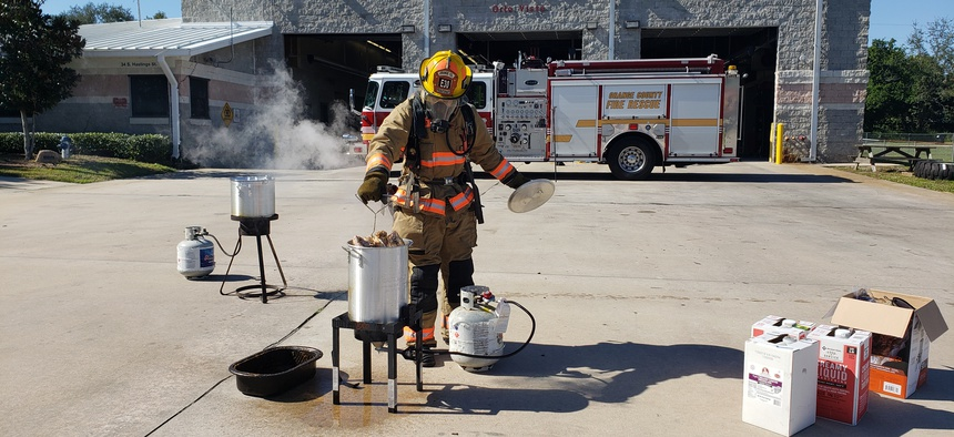 An firefighter from the Orange County Fire Rescue demonstrates how to deep fry a turkey as part of a public safety campaign.
