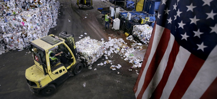 In this Thursday, Sept. 6, 2018, photo, a forklift takes a bundle of paper and cardboard off a conveyor belt at the end of a separating machine at EL Harvey & Sons, a waste and recycling company, in Westborough, Mass.