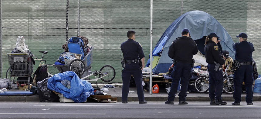 In this March 1, 2016, file photo, San Francisco police officers wait while homeless people collect their belongings in San Francisco.
