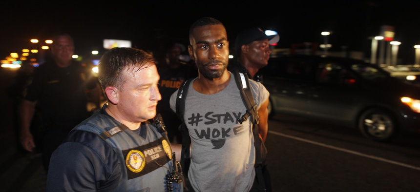 Police officers arrest DeRay Mckesson for blocking Airline Highway during a protest in Baton Rouge, La.