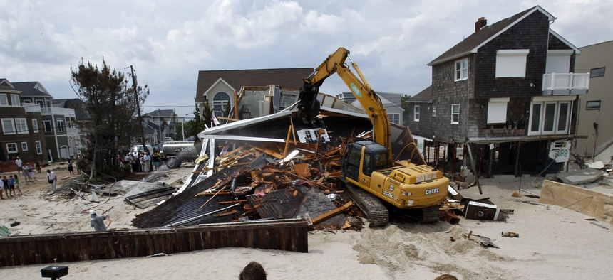 People watch from the beach Wednesday, July 10, 2013, as a home severely damaged by Superstorm Sandy is demolished in the Normandy Beach section of Toms River, N.J.