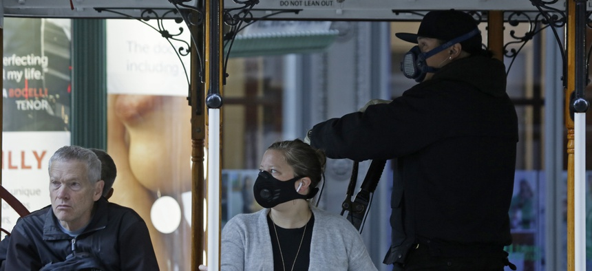 A San Francisco street cable car operator and passenger wear breathing masks to protect against smoke from wildfires on Oct. 28, 2019.