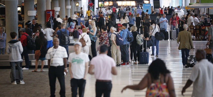 Travelers gather their belongings at baggage claim at the Fort Lauderdale–Hollywood International Airport on Friday, June 29, 2018, in Fort Lauderdale, Fla.