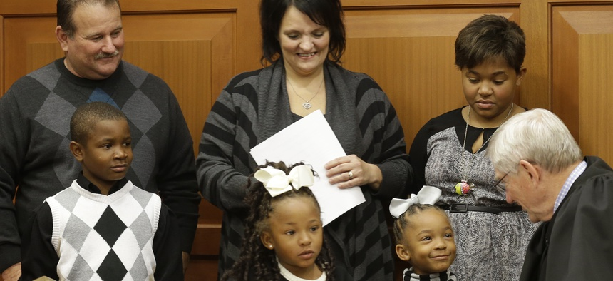 Judge James Cissell talks with twin sisters Lauriana and Laylah after they were adopted by Greg and Robin Smith, along with their brother Laurence and sister Liasia. A record number of children in foster care are being adopted.