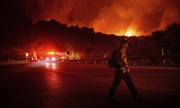 A firefighter crosses Highway 154 while battling the Cave Fire in Los Padres National Forest, Calif., above Santa Barbara on Tuesday, Nov. 26, 2019.